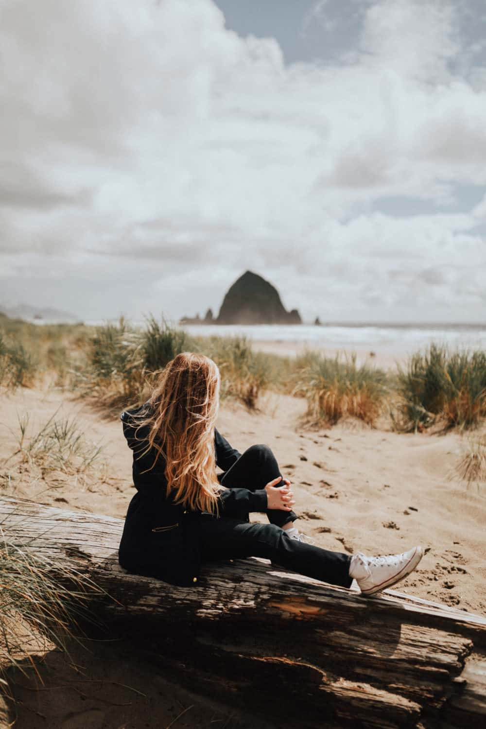 Emily Mandagie sitting at Cannon Beach, Oregon - TheMandagies.com