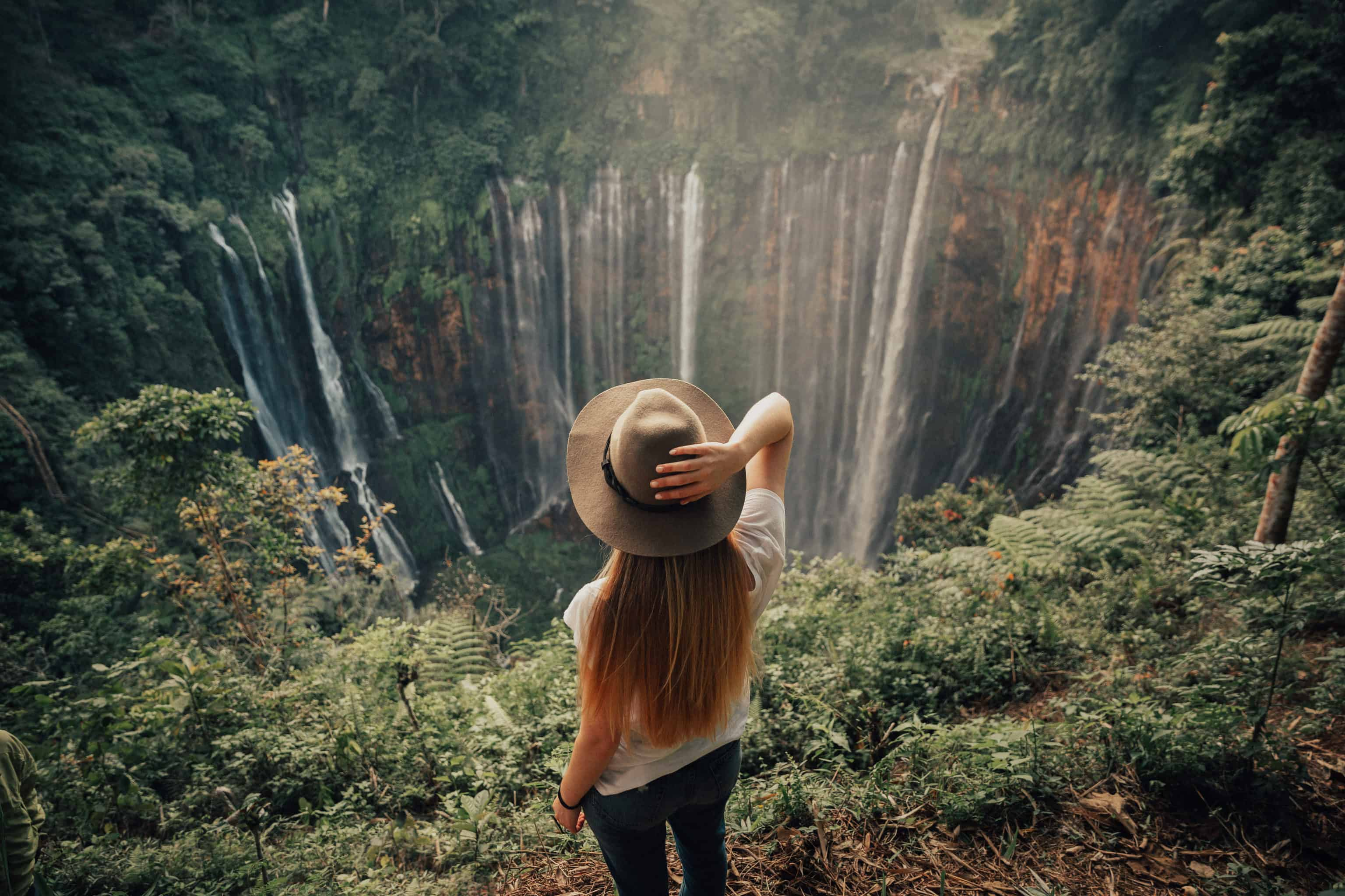 Emily Mandagie standing in front of Tumpak Sewu Waterfall