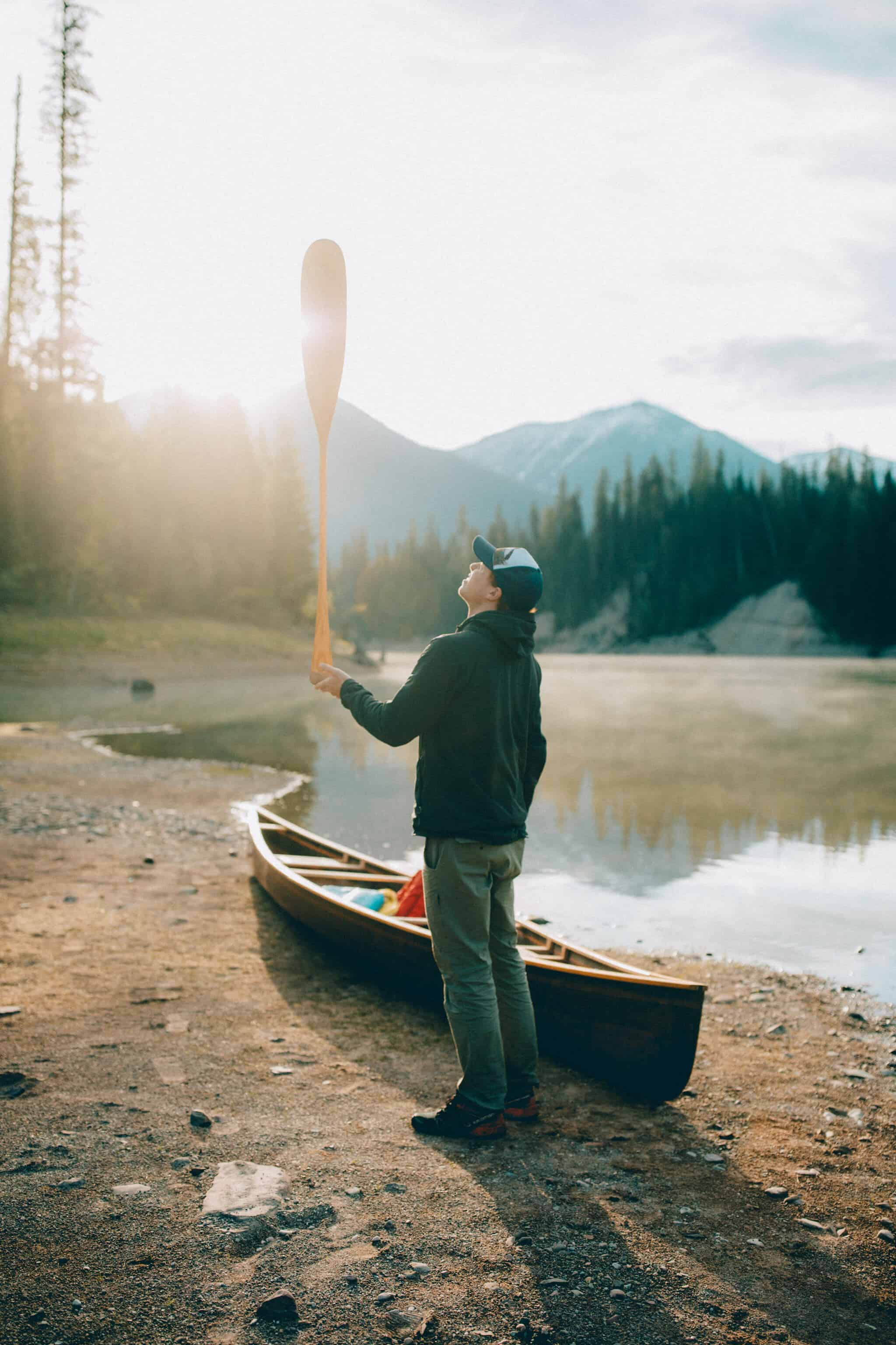 man balancing canoe oar at free camp site