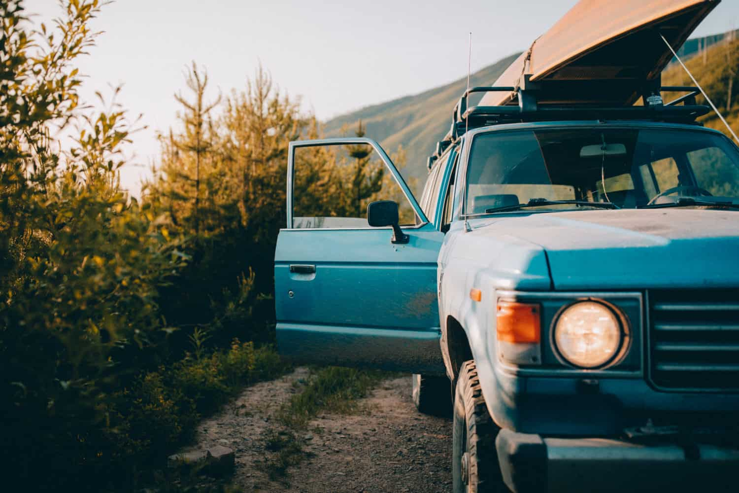 Blue Toyota FJ Land Cruiser with canoe on top