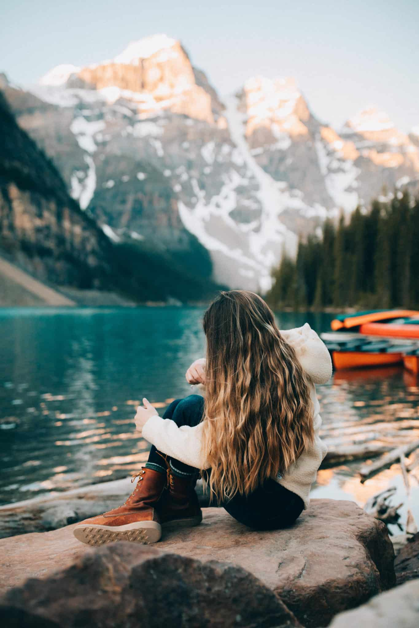 Moraine Lake Sunrise - Emily Mandagie wearing Red Wing Boots near colorful canoes