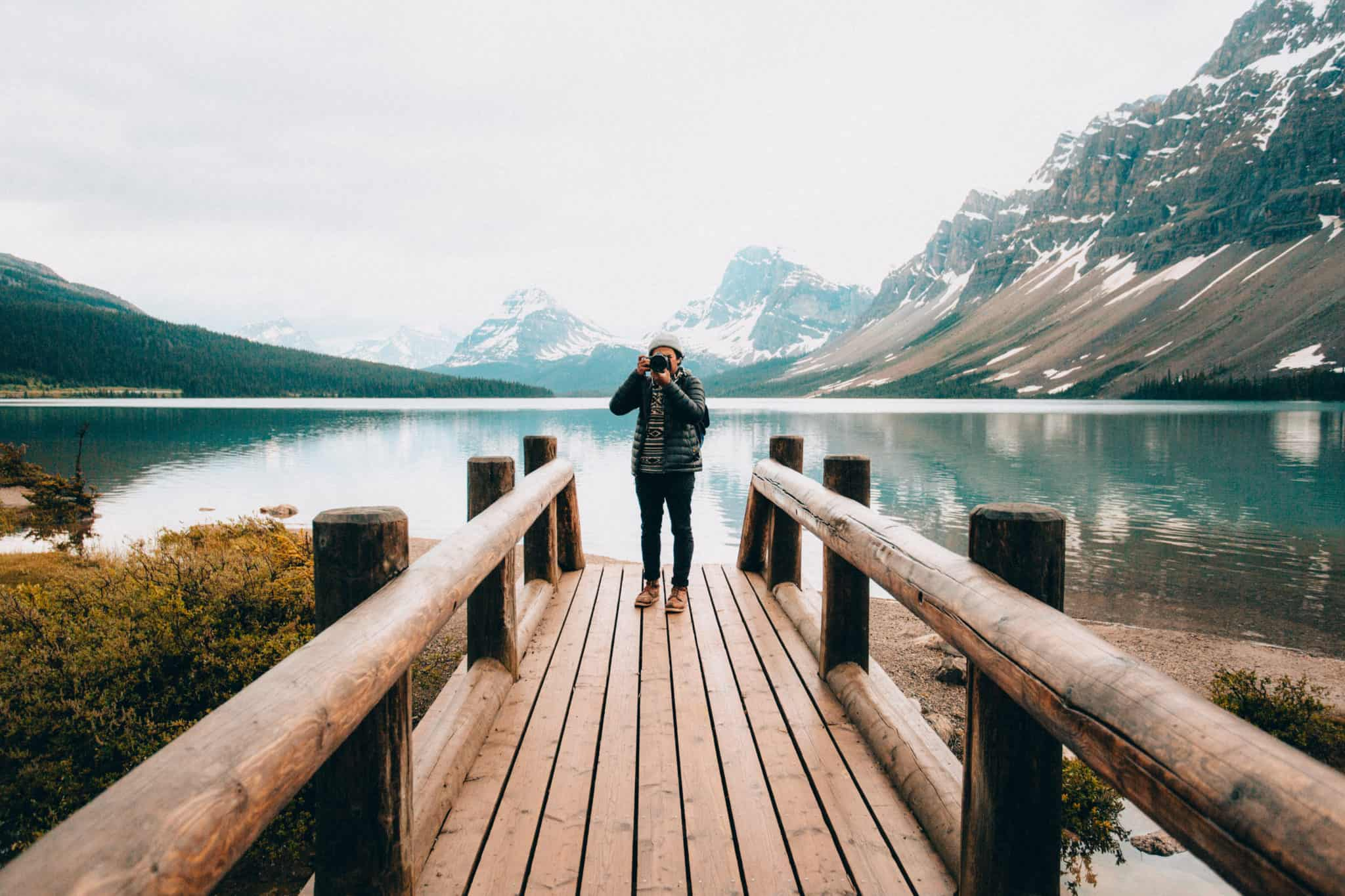 Berty Mandagie standing on Bow Lake wooden bridge, Banff National Park, Alberta Canada