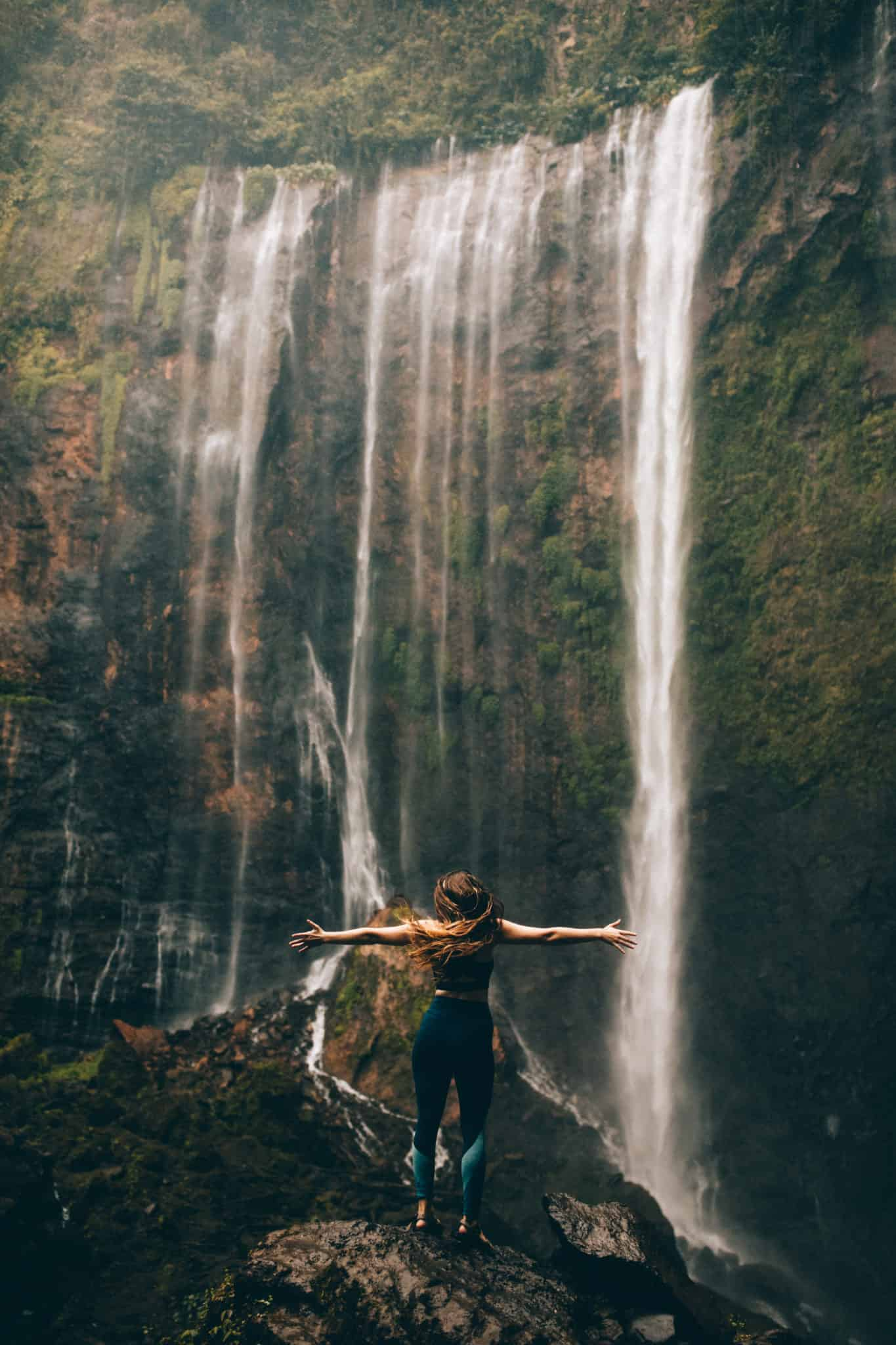 Emily standing below Tumpak Sewu Waterfall