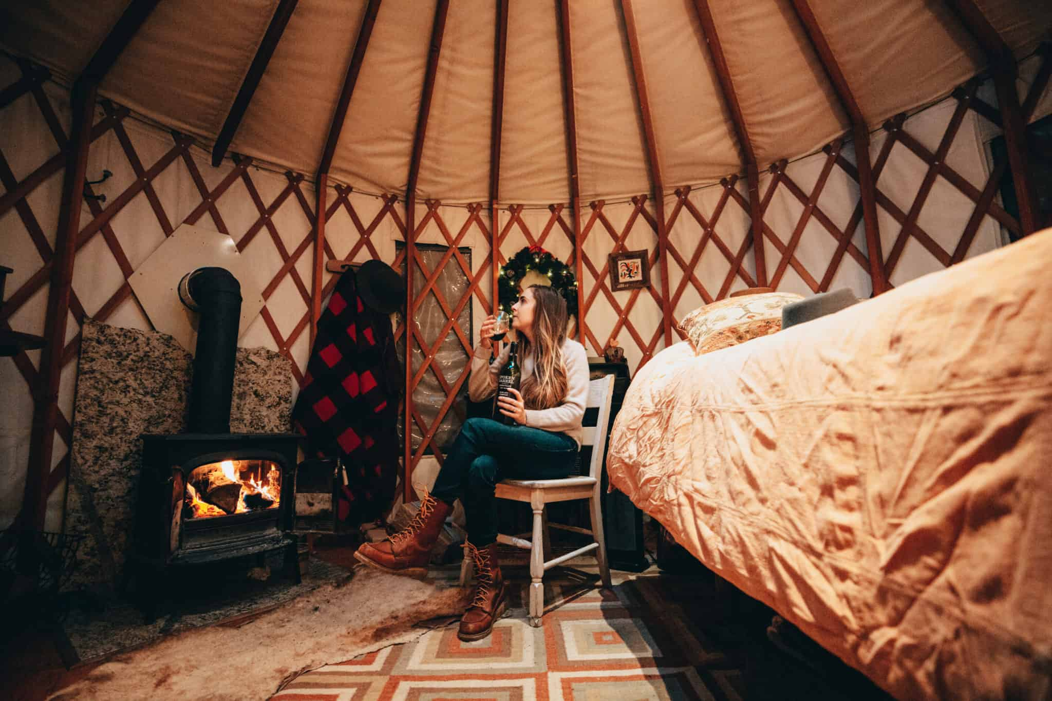 Emily drinking wine inside of yurt in north idaho