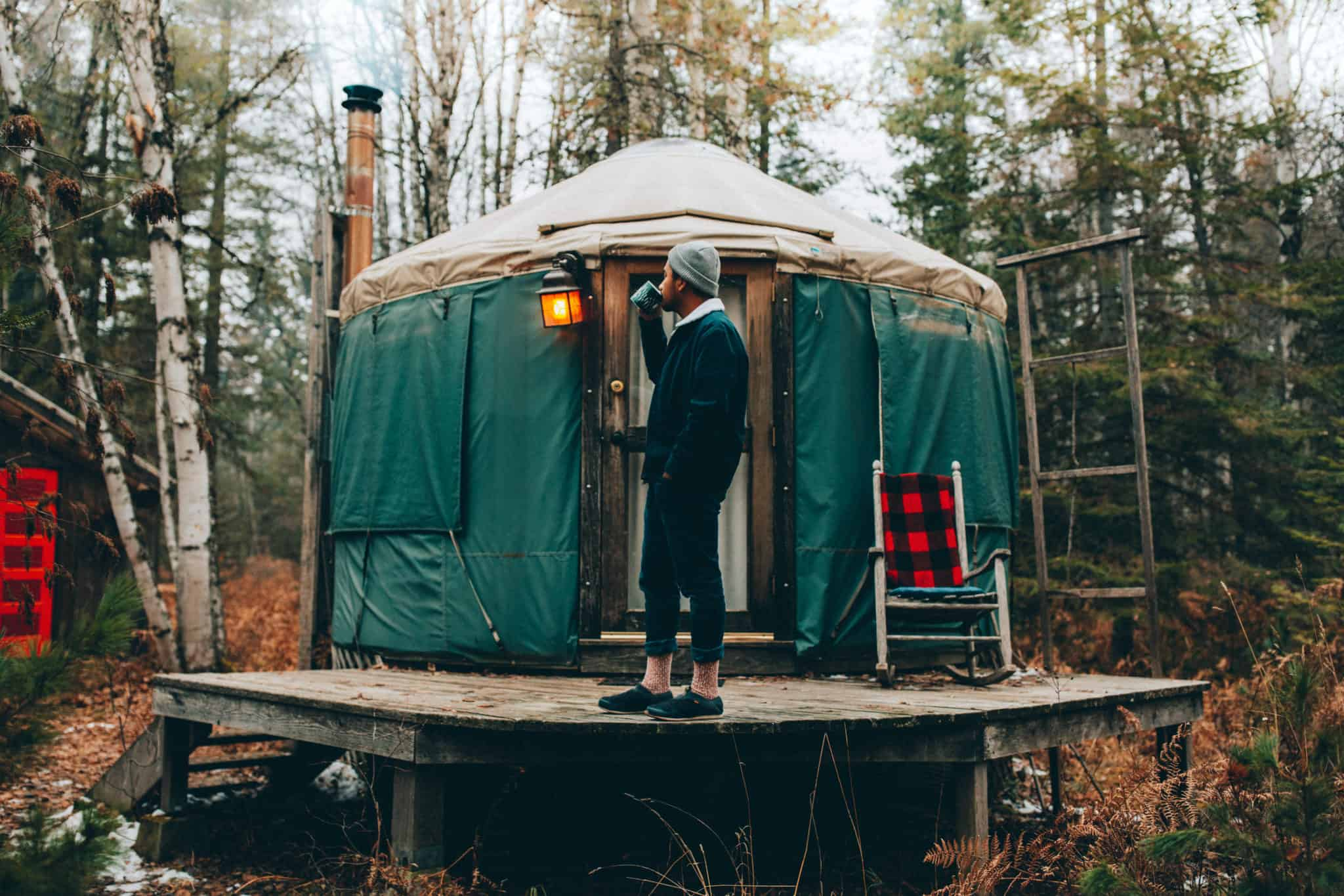 Berty Mandagie drinking coffee outside of a yurt
