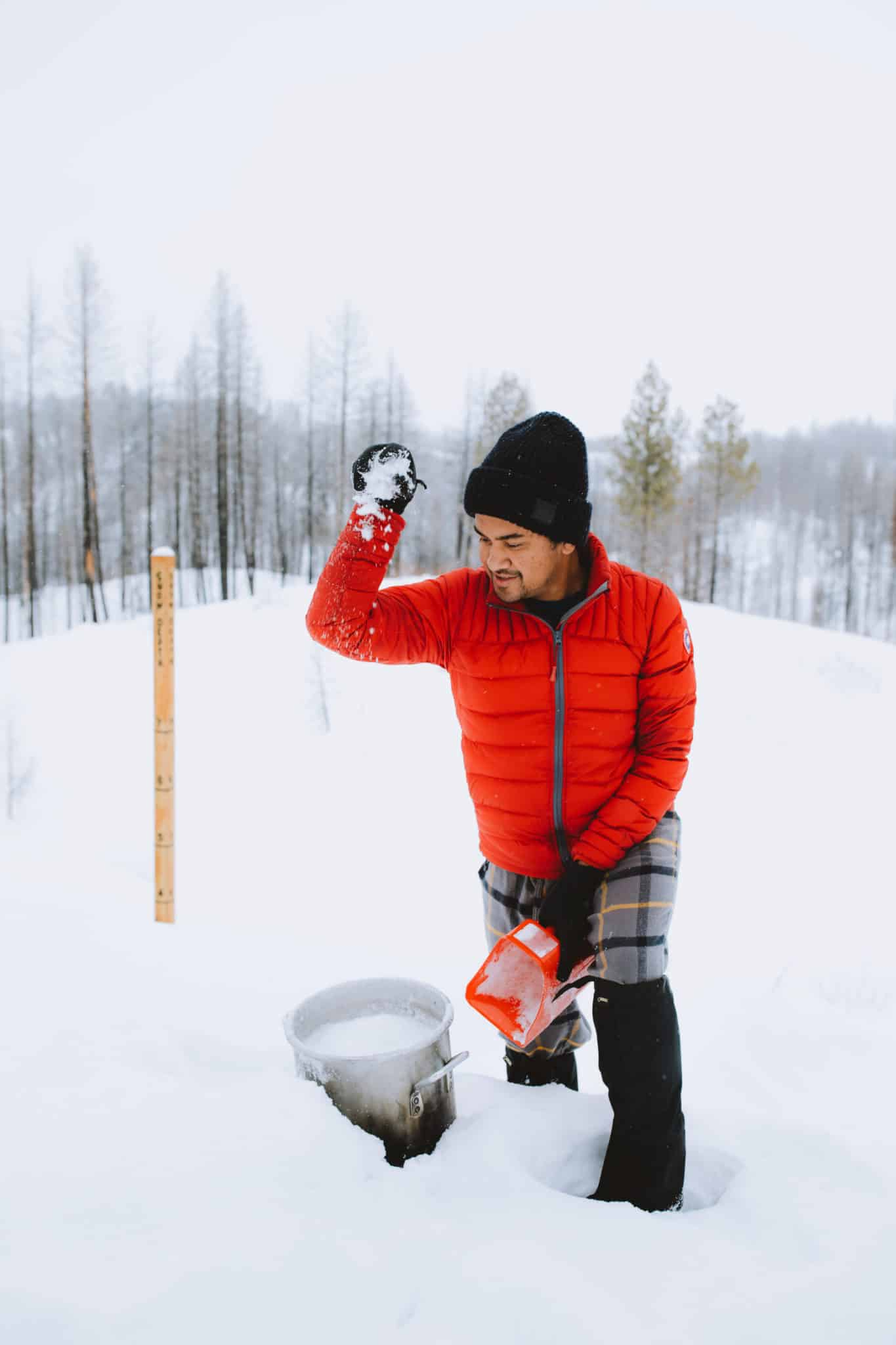 Berty Mandagie collecting snow in a pot