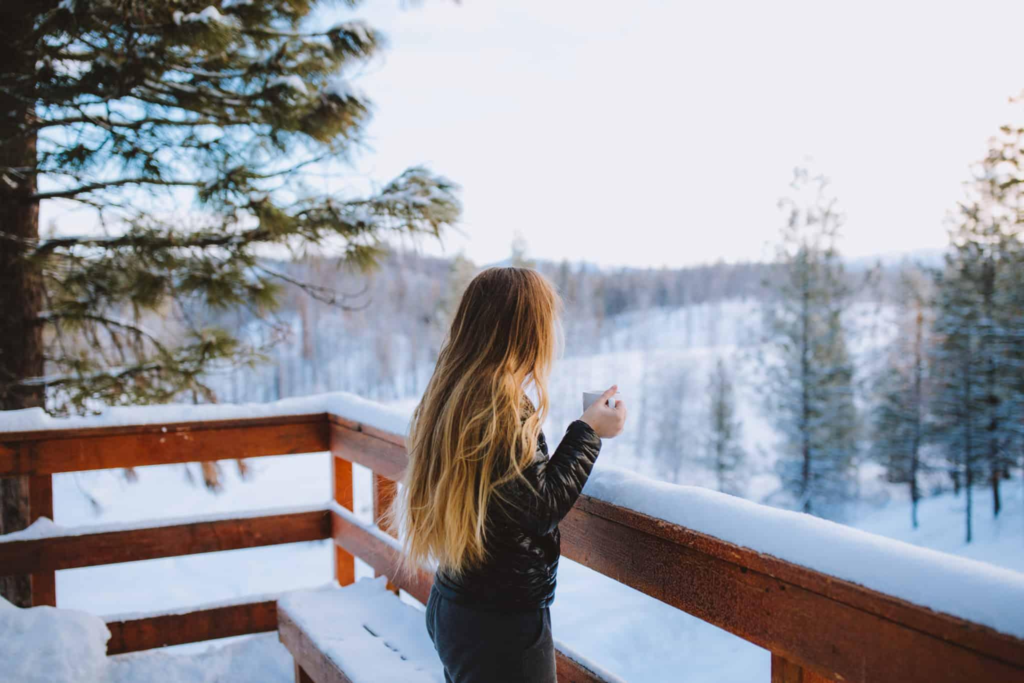 Emily standing on yurt deck drinking coffee