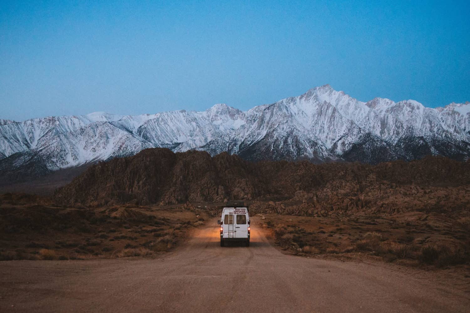 Van driving on Alabama Hills before sunrise