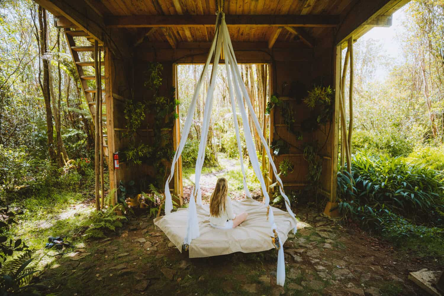 Emily sitting on swinging bed in Hawaii Treehouse - TheMandagies.com