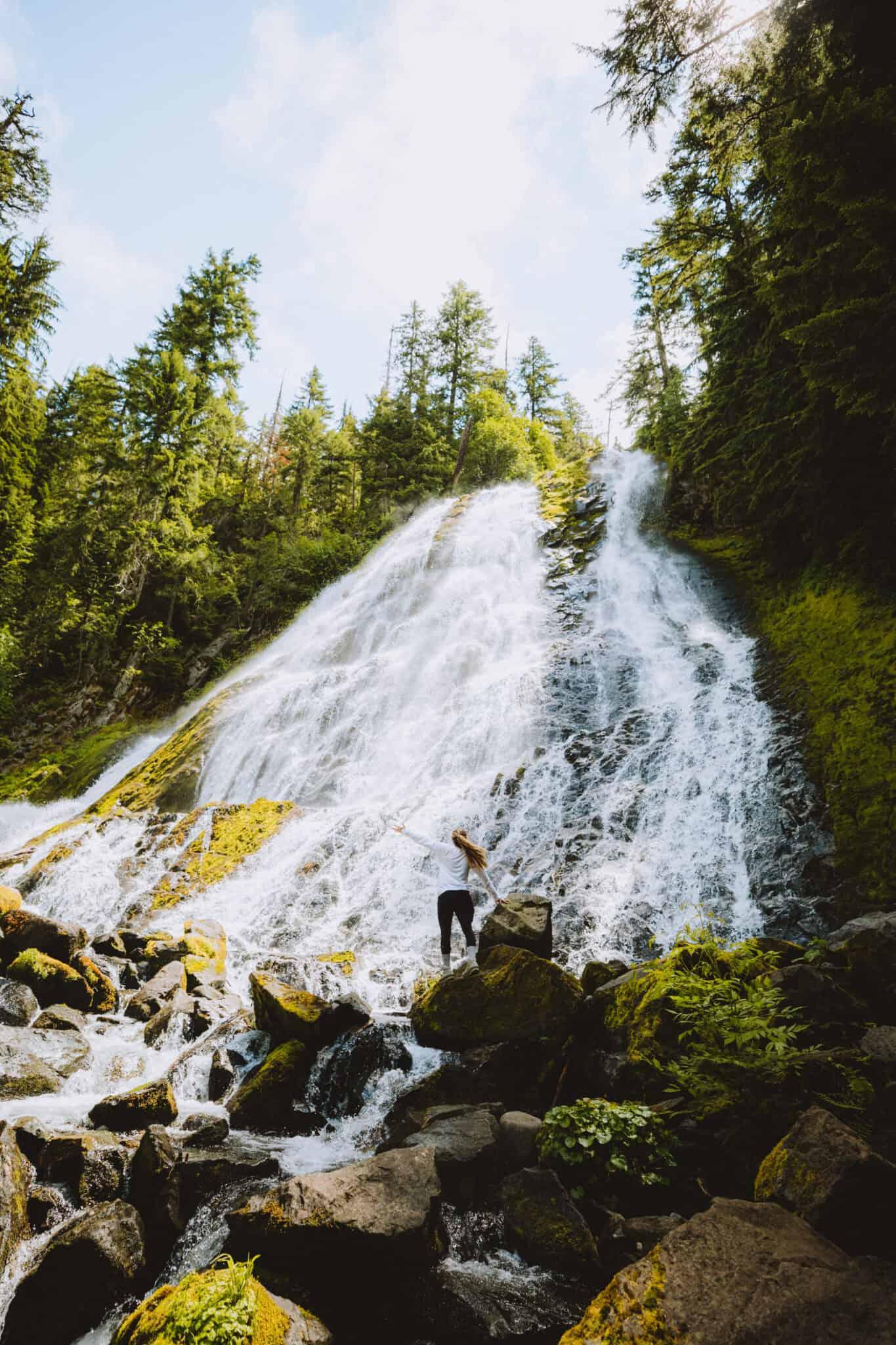 Emily standing at base of Diamond Creek Falls