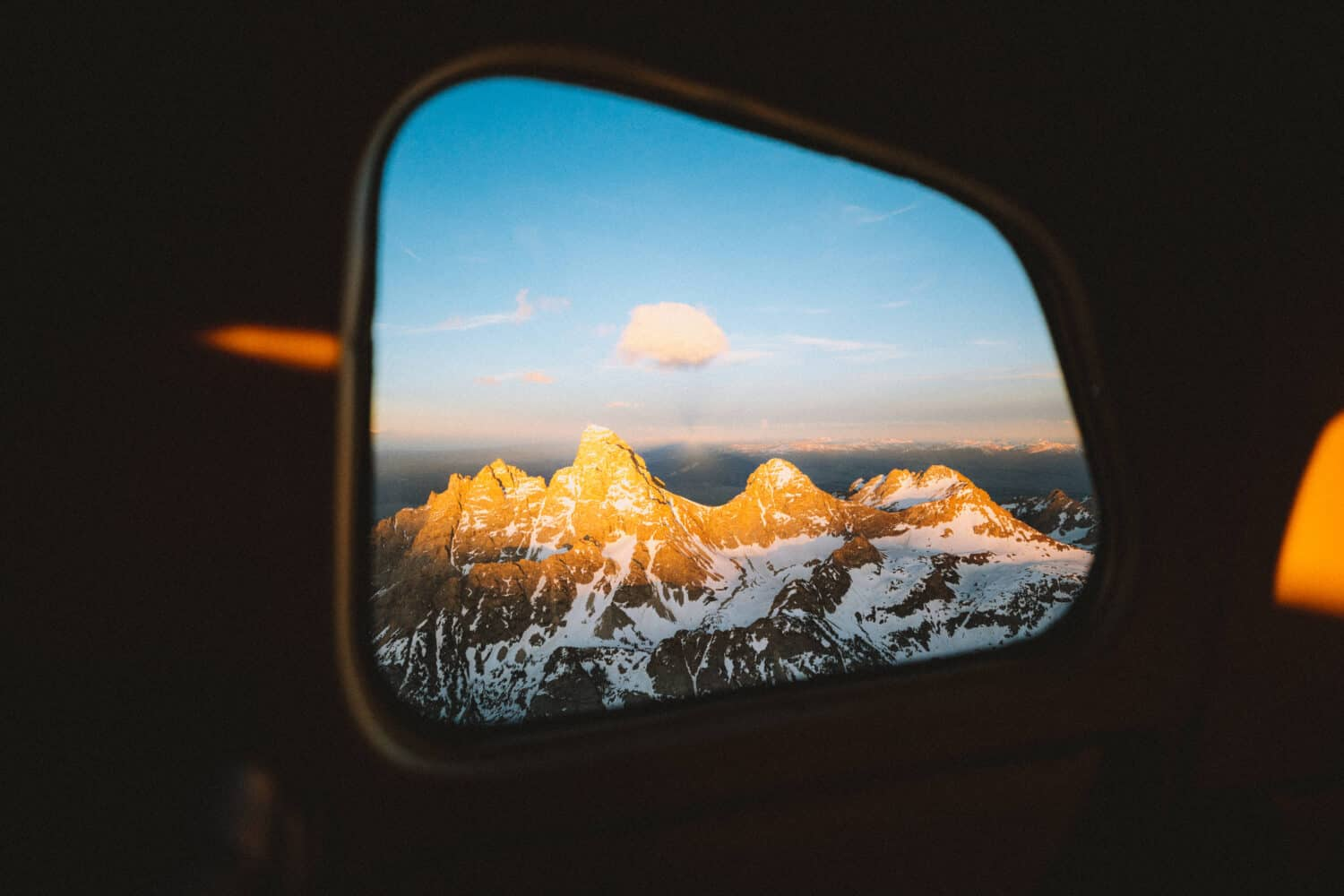 View of the Grand Tetons from plane window - TheMandagies.com