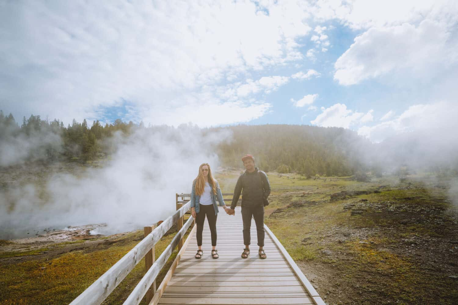 Emily and Berty Mandagie standing on boardwalk in Yellowstone