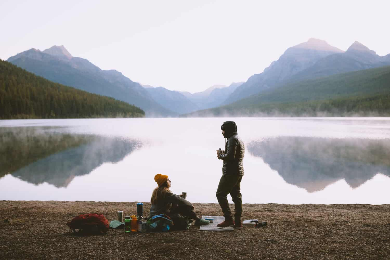 Berty Mandagie and Emily Mandagie sitting by Bowman Lake, Glacier