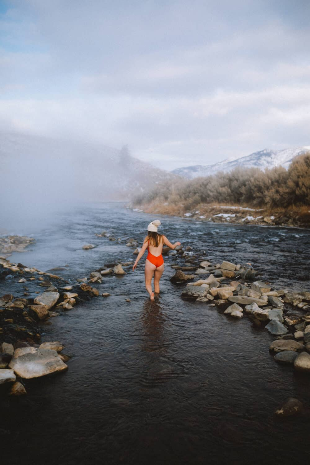 Emily Mandagie walking in the Boiling River, Yellowstone - TheMandagies.com