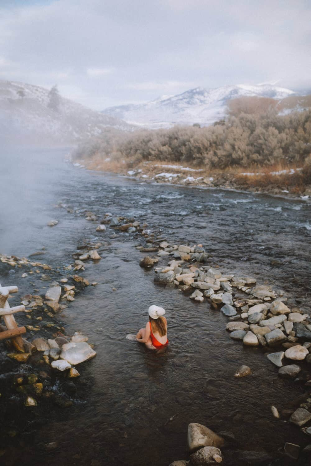 Emily Mandagie in red swimsuit in the Boiling River Yellowstone - TheMandagies.com