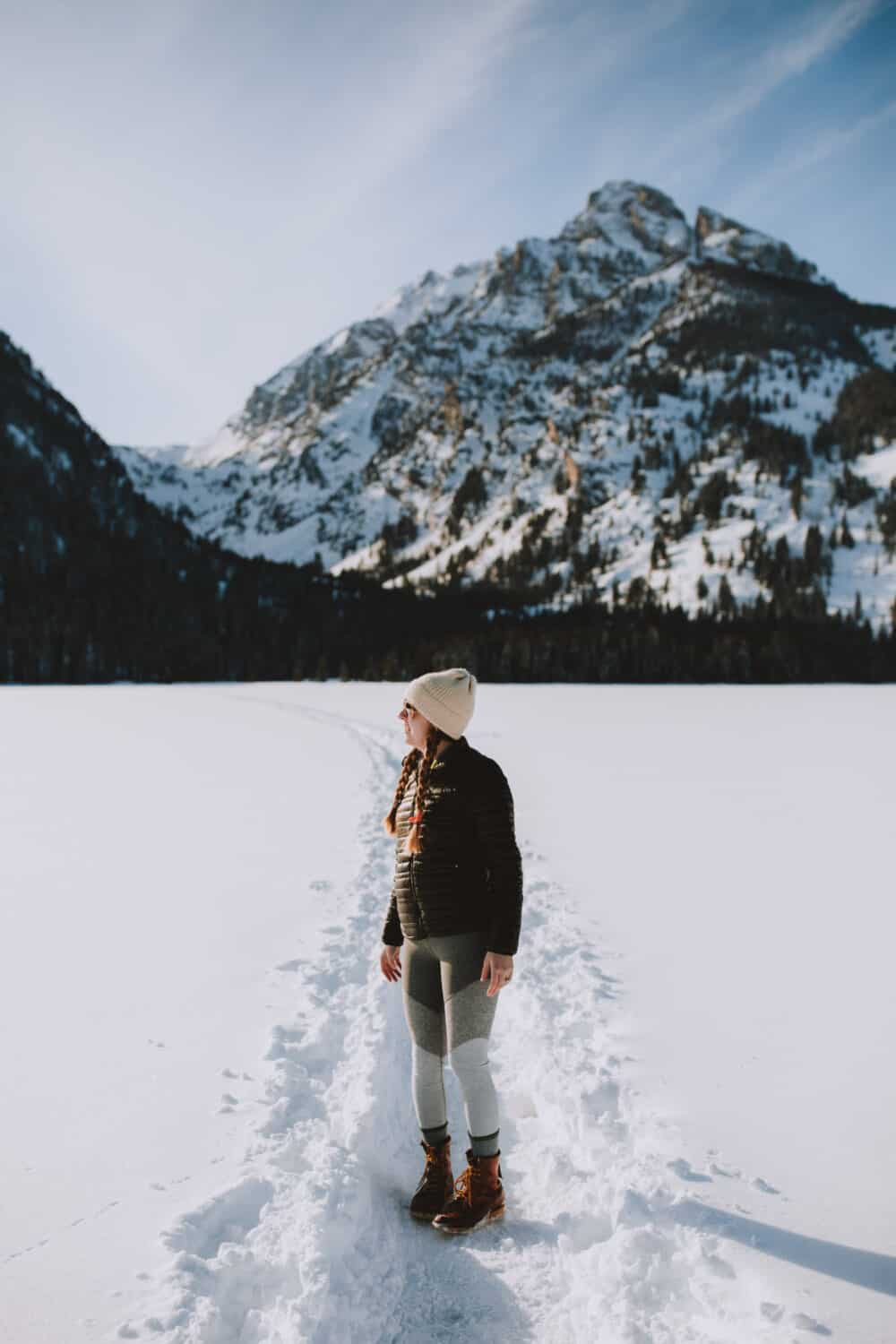 Emily Mandagie standing on Frozen Taggart Lake in Wyoming - TheMandagies.com