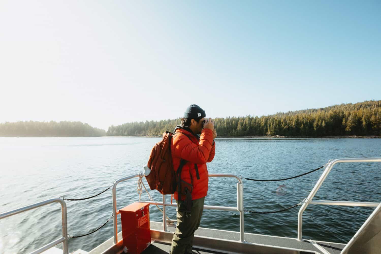 Berty Mandagie standing exterior of speed boat in Tofino, BC - TheMandagies.com