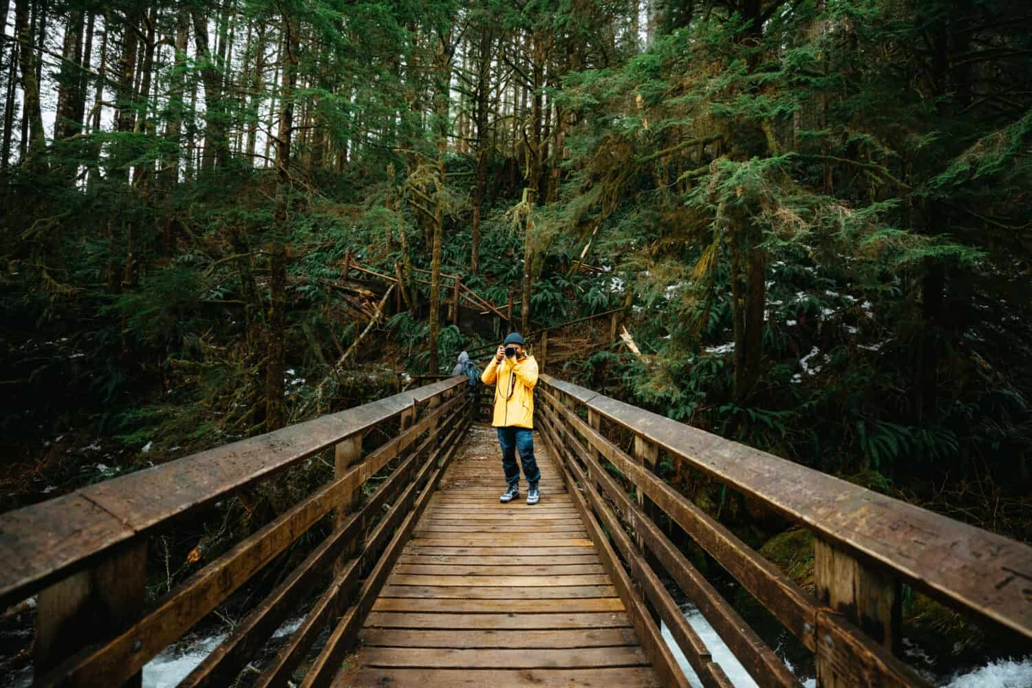Berty Mandagie standing on wooden bridge on Wallace Falls Trail, Washington - TheMandagies.com