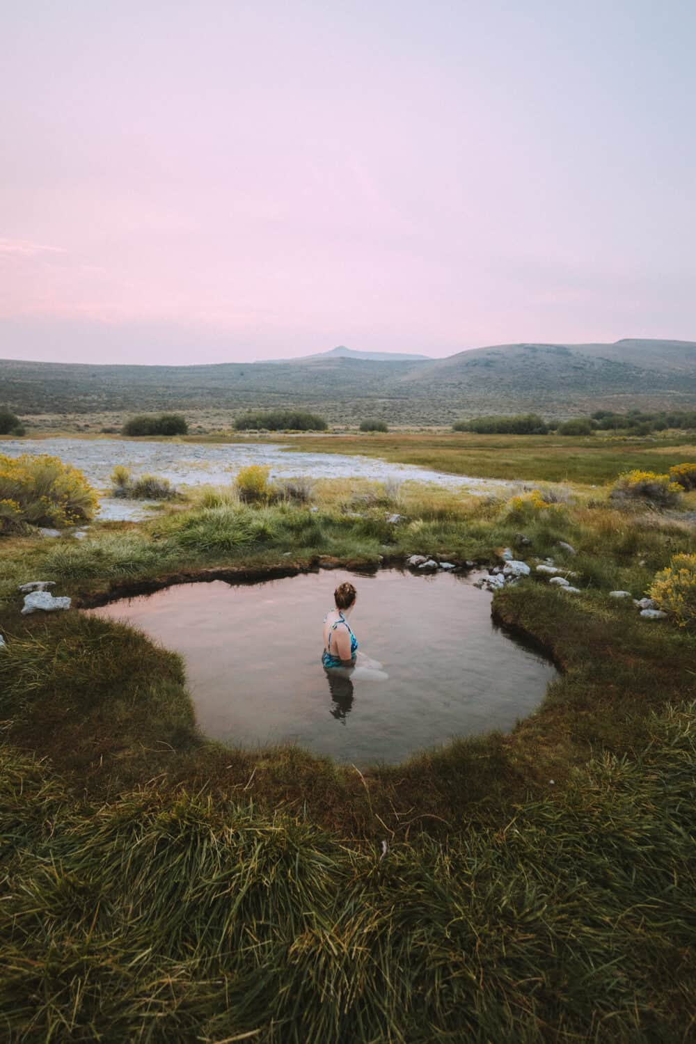 Emily Mandagie sitting in Hart Mountain Hot Springs in Eastern Oregon