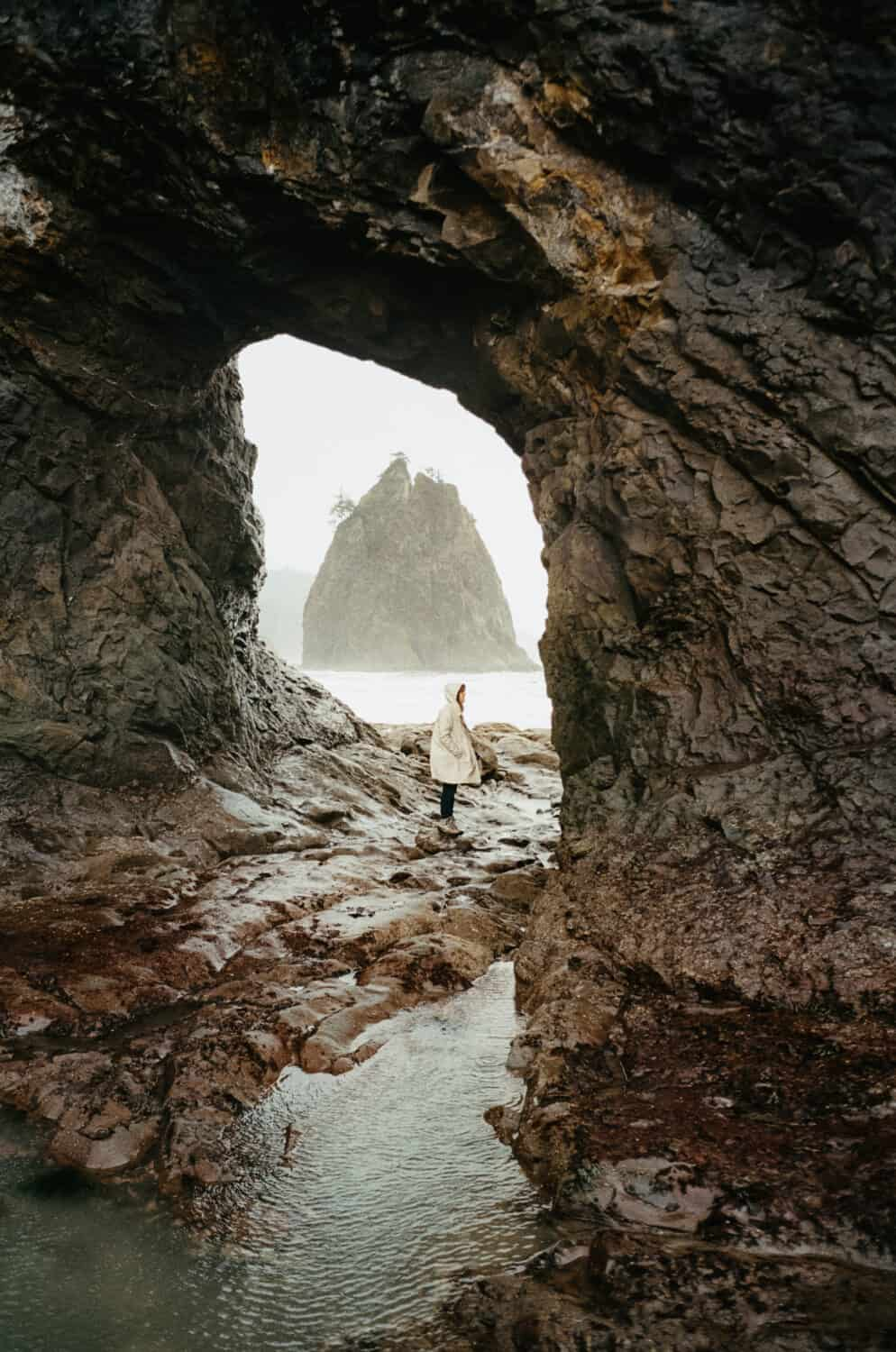 Emily Mandagie standing in Hole In The Wall, Rialto Beach WINTER SEASON - TheMandagies.com