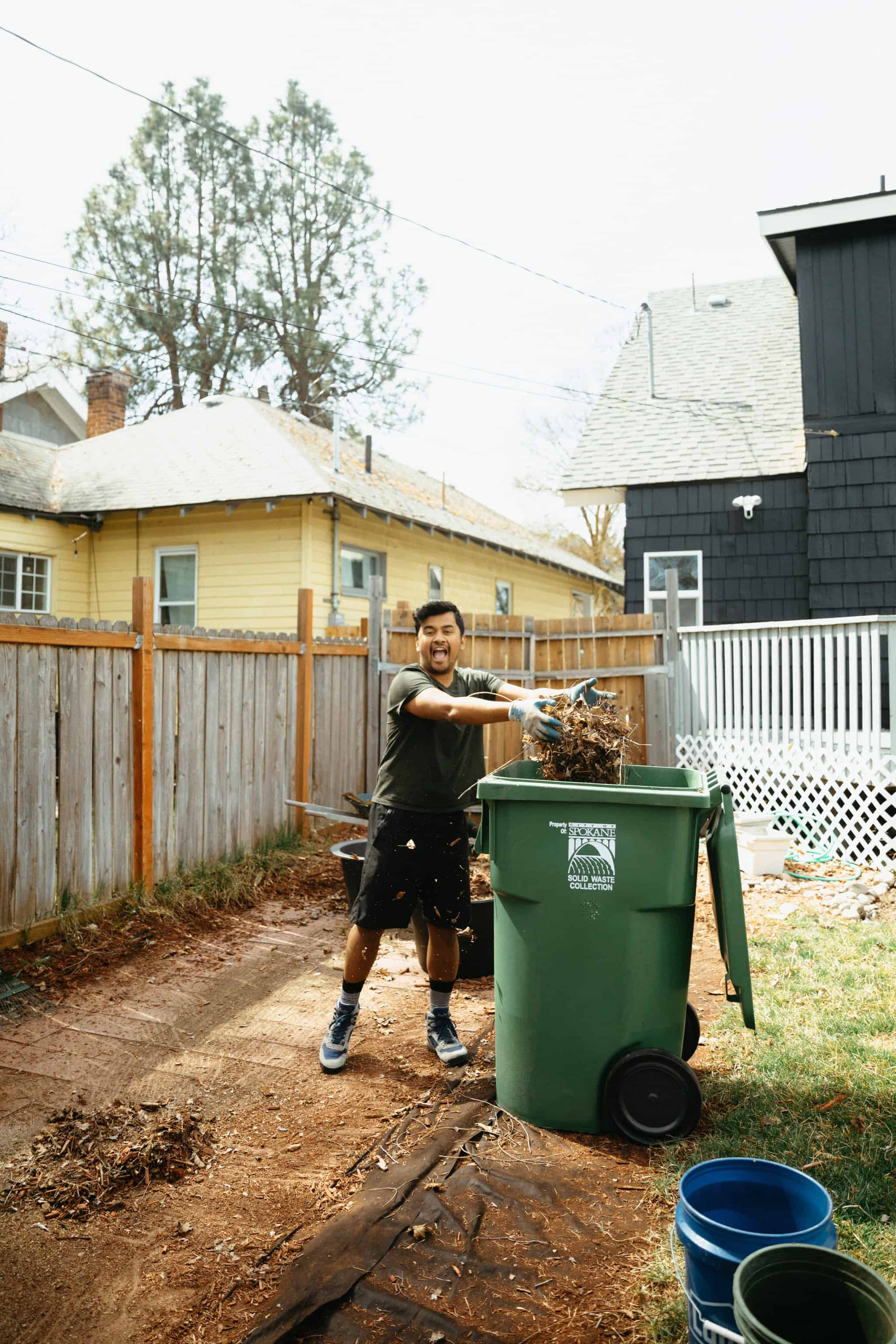 Berty Mandagie cleaning up backyard for easy fire pit