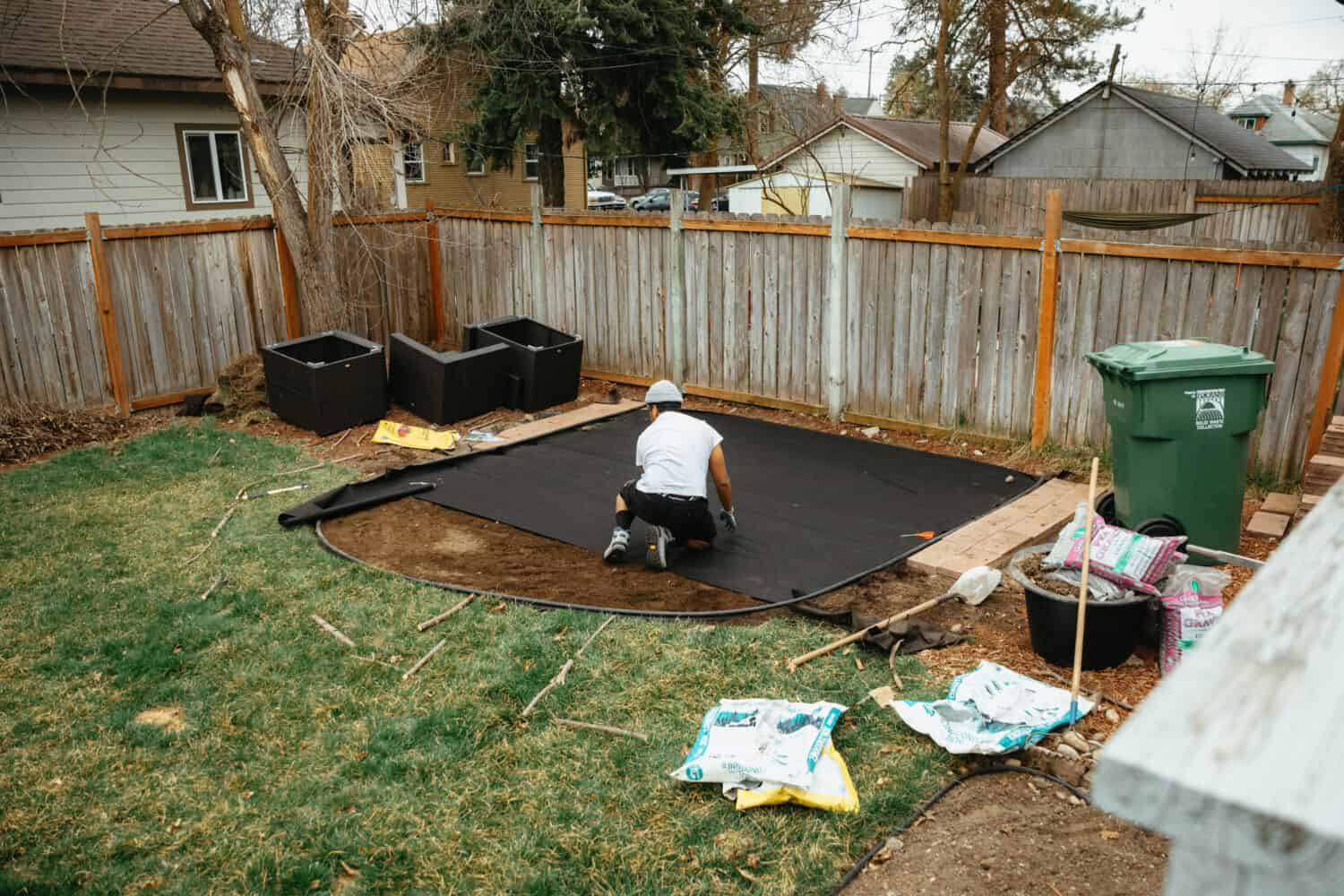 Berty Mandagie laying down the weed paper - backyard fire pit ideas - TheMandagies.com