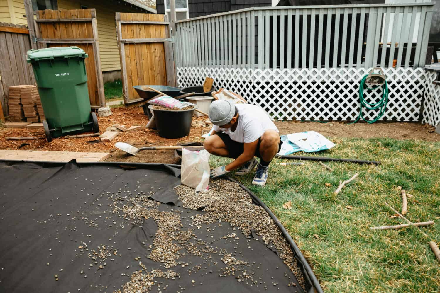 Spreading pea gravel into the backyard fire pit area - themandagies.com