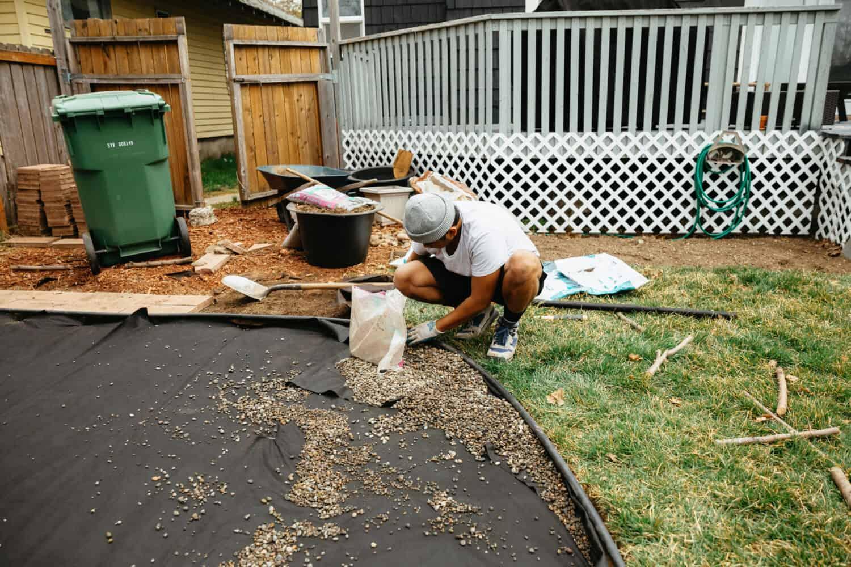 Spreading pea gravel into the backyard fire pit area - themandagies.com
