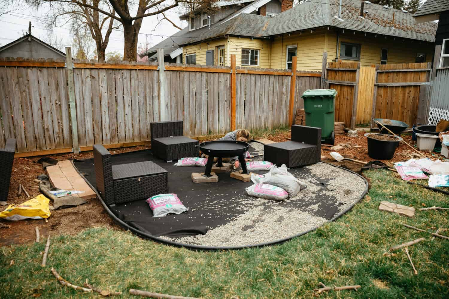 Emily Mandagie arranging portable fire pit on stones - TheMandagies.com