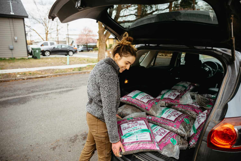 Emily Mandagie unloading pea gravel from the car - TheMandagies.com
