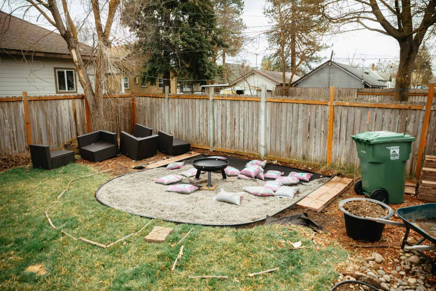 Spreading gravel into rock fire pit area - TheMandagies.com