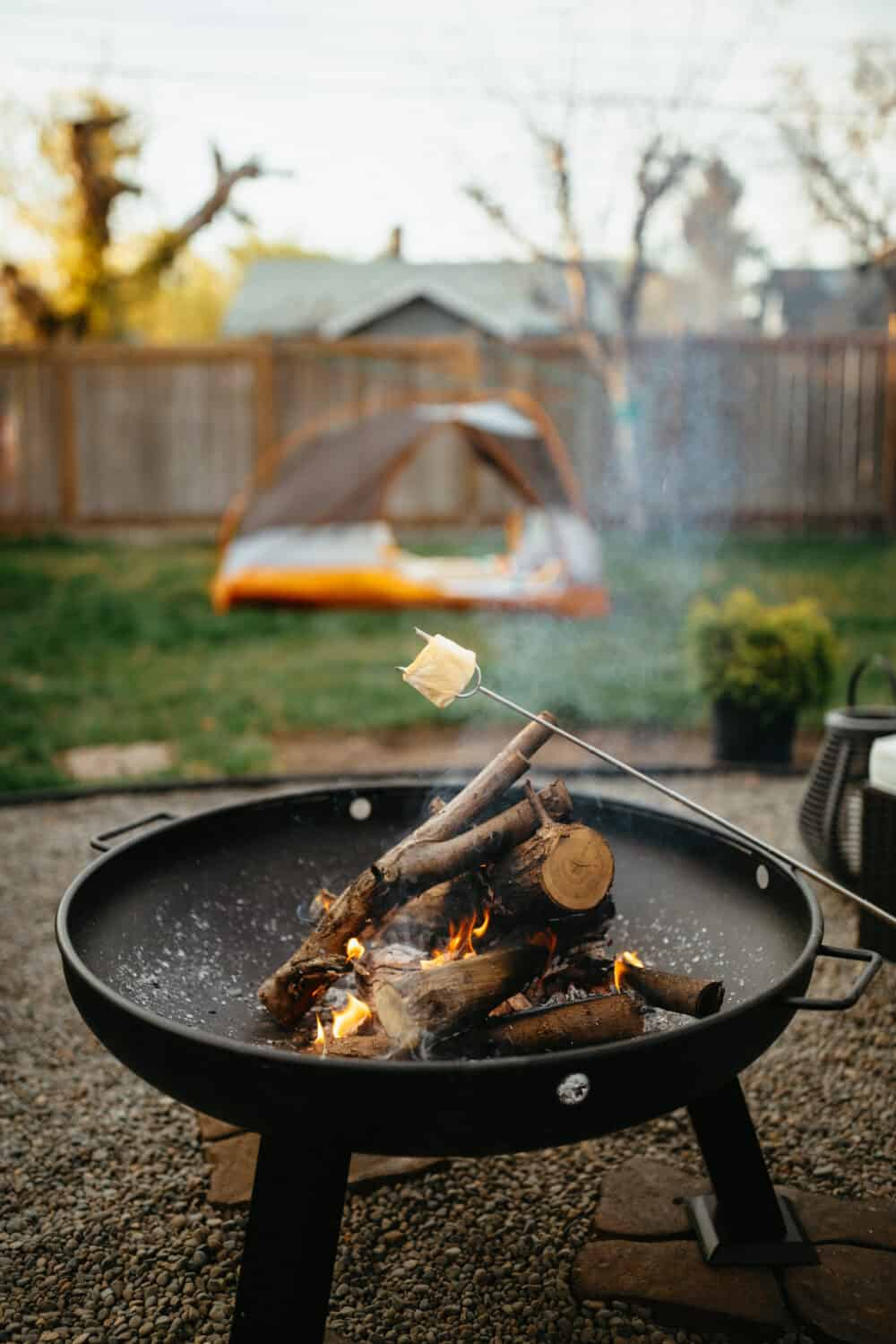 Roasting S'more around simple fire pit in backyard - TheMandagies.com