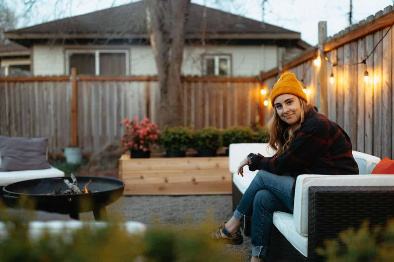 Emily Mandagie sitting near DIY Backyard Fire Pit