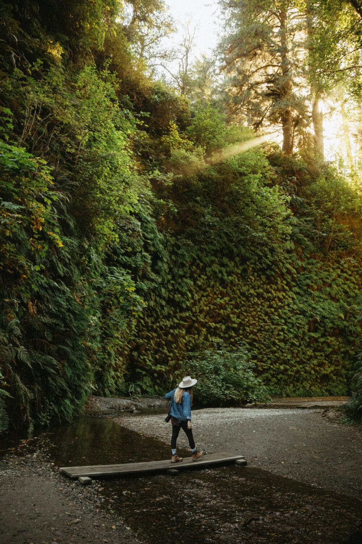 Emily Mandagie crossing a creek on Fern Canyon Trail - California