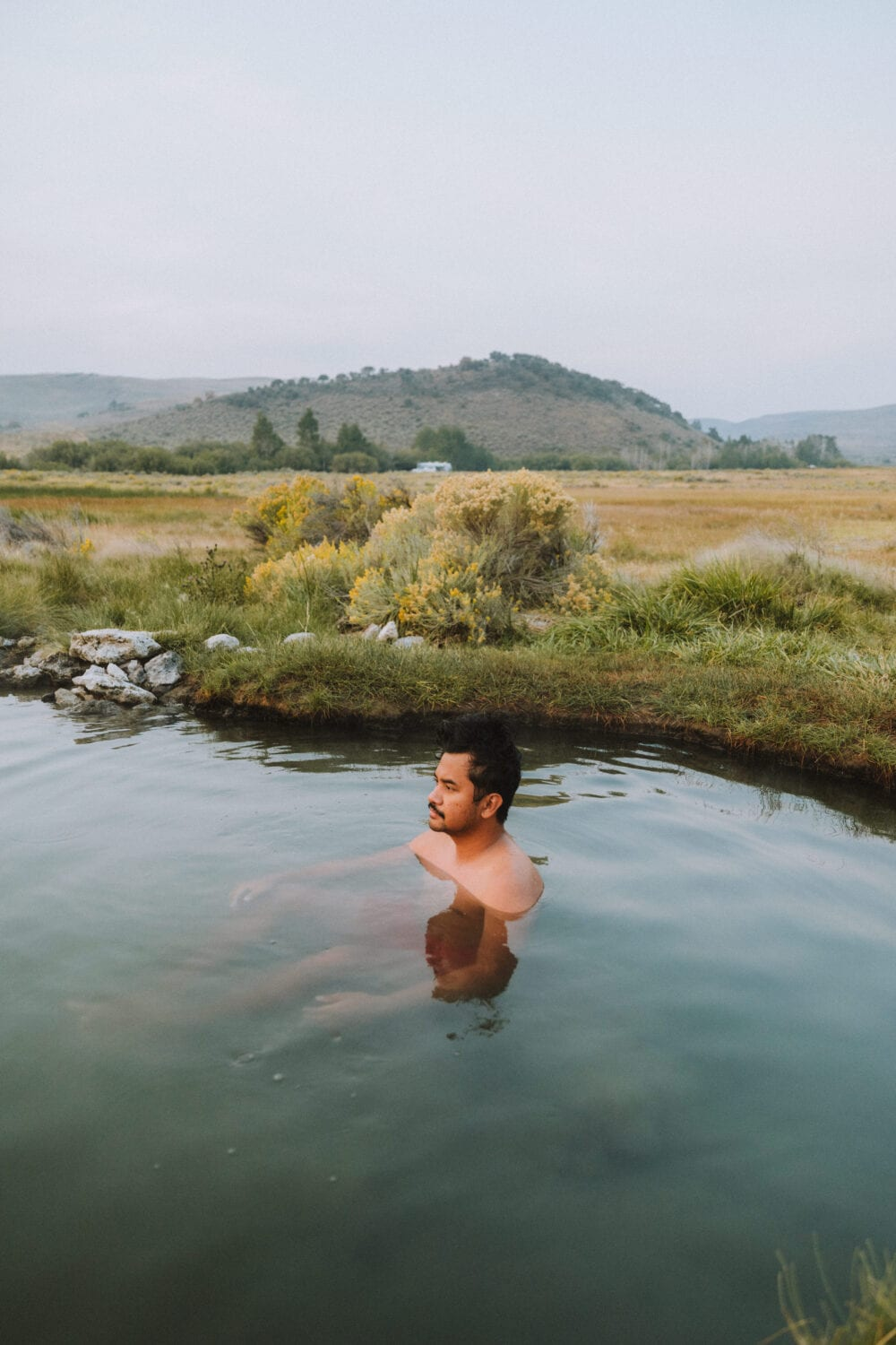 Berty Mandagie sitting in natural oregon hot springs