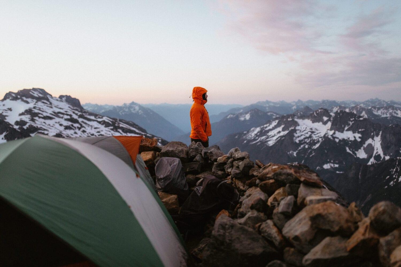 Man in orange jacket looking at the North Cascade Mountain Range in Washington during sunset.