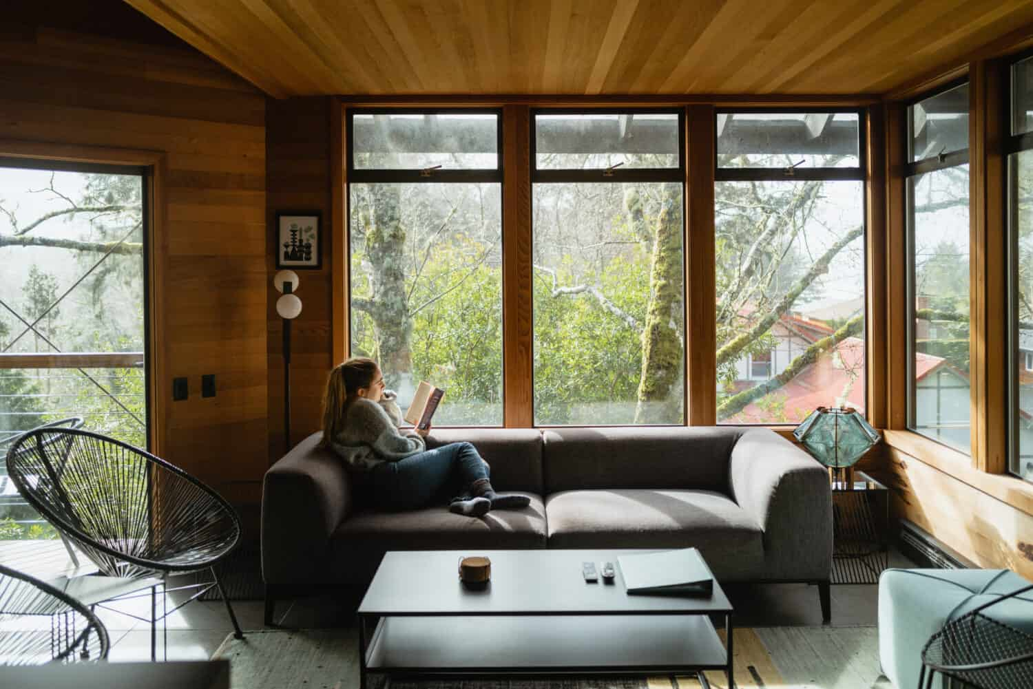 Emily Mandagie sitting in livingroom in Oregon Coast Modern