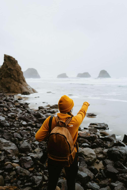 Emily Mandagie pointing to sea stacks on the Oregon Coast