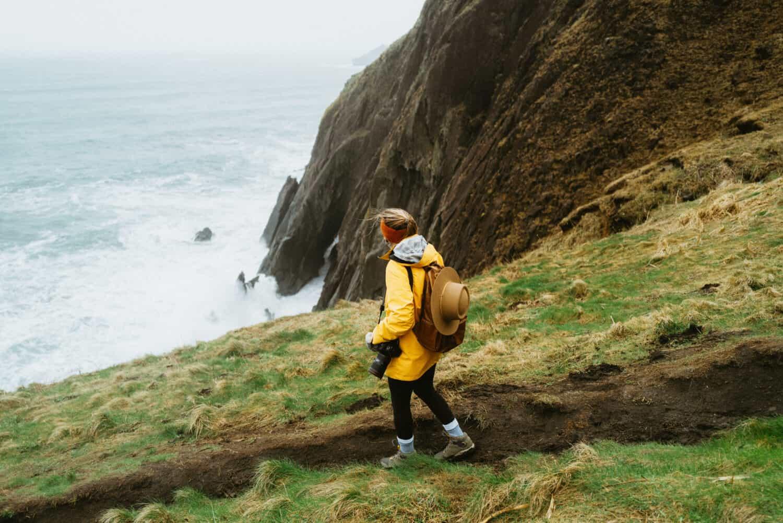 Emily Mandagie walking on Elk Flats Trail near the cliffside on the Oregon Coast