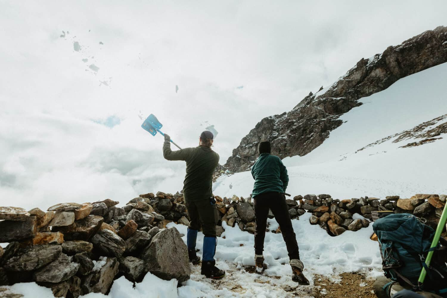 Shoveling snow out of the rock ring structures at Sahale Glacier Camp