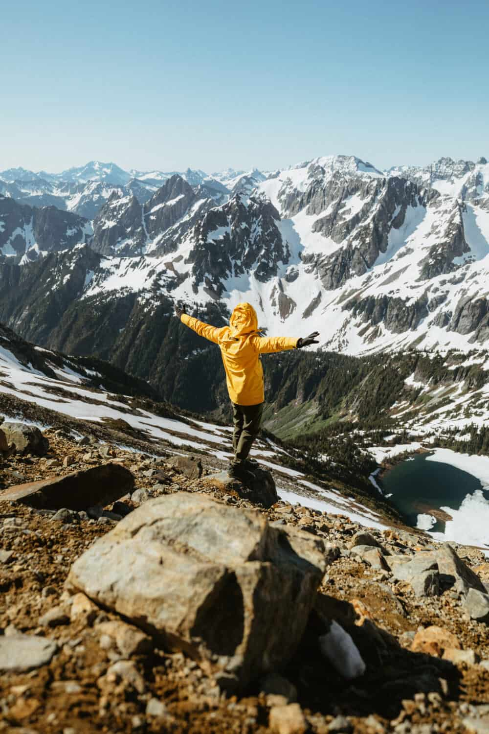 Man in yellow jacket, standing in front of North Cascade Mountain range in July