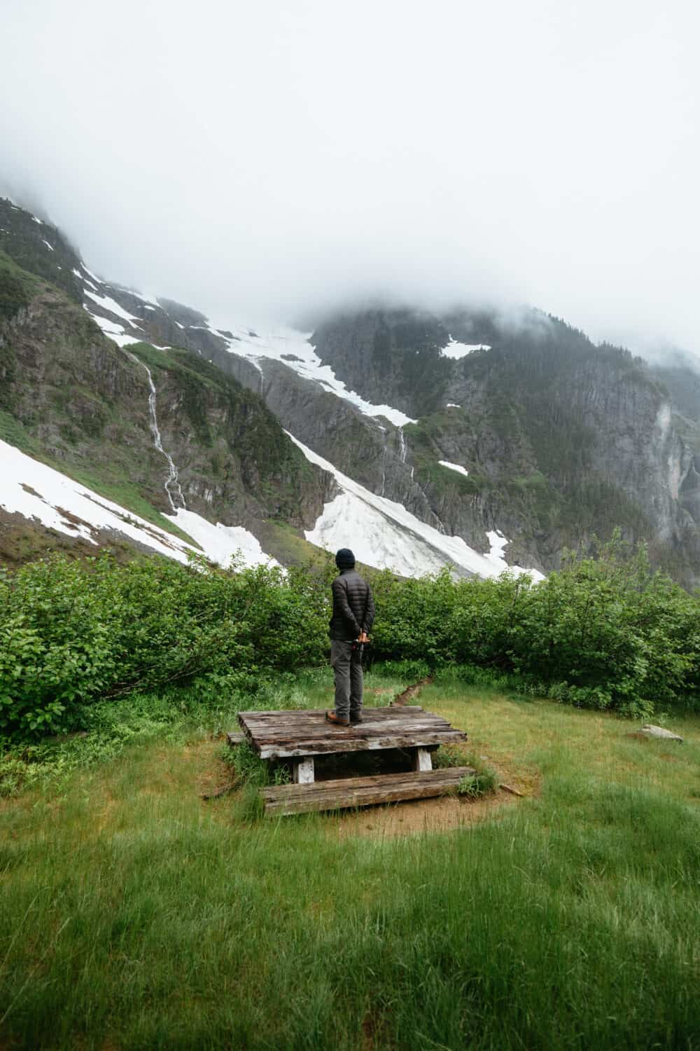 Man standing on a picnic table, with foggy mountains in the distance