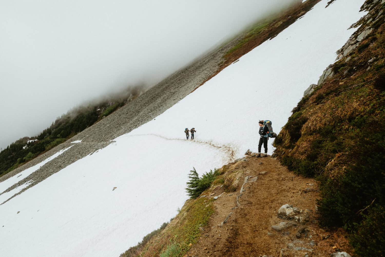 Hiking a snowy trail Cascade Pass Trail to Sahale Glacier Camp.