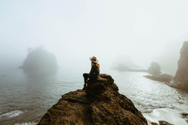 Emily Mandagie sitting on a rock at the Oregon Coast - Pacific Northwest